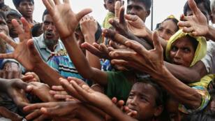 لاجئون من أقلية الروهينغا خلال توزيع أغذية في مخيم كوتوبالونغ في أوخيا بالقرب من الحدود بين بنغلاديش وبورما