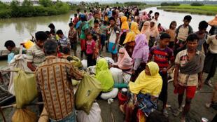 نساء وأطفال من أقلية الروهينغا يفرون من العنف