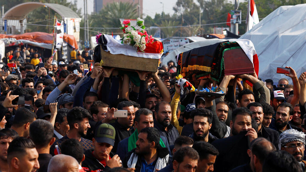 المشيعون يحملون التابوت خلال جنازة أحد المتظاهرين الذي قُتل في مظاهرة مناهضة للحكومة ليلة الأحد في النجف