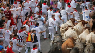 أشخاص يشاركون في آخر أيام مهرجان سان فيرمين السنوي لركض الثيران في مدينة بامبلونا الإسبانية