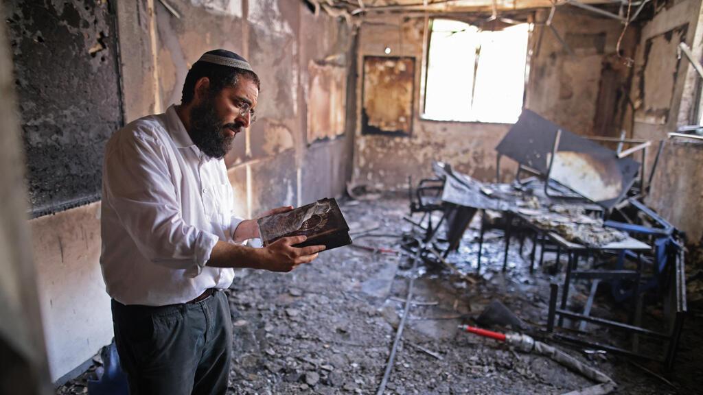حاخام يتفقد الأضرار التي لحقت بمدرسة يهودية في مدينة اللد وسط إسرائيل