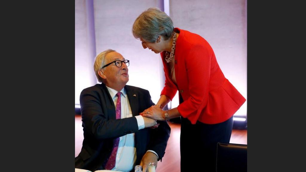 رئيسة الوزراء البريطانية تيريزا ماي تصافح رئيس المفوضية الأوروبية جان كلود يونكر