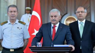 رئيس الوزراء التركي بن علي يلديريم وبجانبه رئيس أركان الجيش خلوصي آكار في مؤتمر صحفي أمام مكتبه