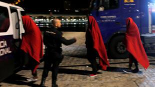 عناصر من الشرطة الإسبانية يرافقون مهاجرين إلى مراكز ايواء