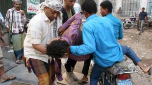 متطوعون يحملون صبيا أصيب بقذيفة أثناء القتال بين الموالين للحكومة والحوثيين .تعز 29 سبتمبر 2015