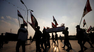 متظاهرون  يحملون كفن أشخاص قتلوا في التظاهرات، البصرة، العراق