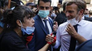 الرئيس الفرنسي إيمانويل ماكرون يستمع إلى سيدة لبنانية تشكو إليه خلال زيارته لشارع مدمر في بيروت يوم 6 أغسطس 2020