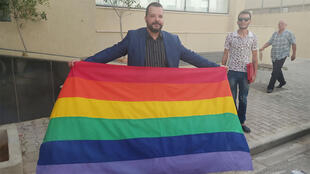 منير بعطور حاملاً علم فخر المثليين