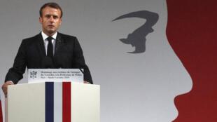 الرئيس ماكرون يخطب وخلفه ملصق لماريان رمز الجمهورية الفرنسية وقيمها