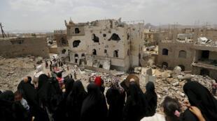 يمنيون ينظرون إلى أنقاض المنازل التي دمرتها غارة جوية سعودية في العاصمة اليمنية صنعاء 21 يونيو