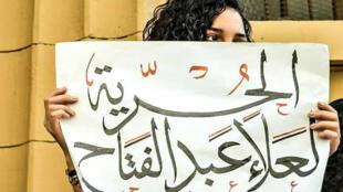 سناء سيف ترفع لافتة مطالبة بالحرية لأخيها المعتقل علاء عبد الفتاح