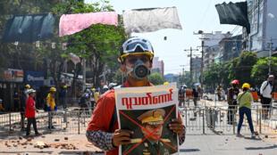 متظاهر يحمل ملصقًا يظهر قائد القوات المسلحة في ميانمار الجنرال مين أونغ هلاينغ خلال مظاهرة ضد الانقلاب العسكري في يانغون، في 9 مارس 2021