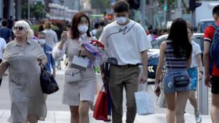 أشخاص يتوجولون مع قناع واقٍ بسبب انتشار فيروس كورونا، سنغافورة