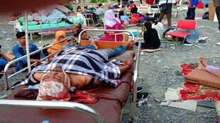 الناجون من الزلزال يستريحون على أسرة خارج مستشفى في بالو