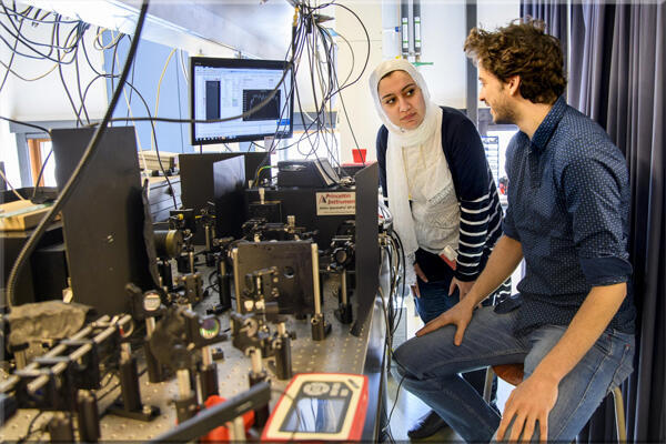باحثان يقومان بضبط الإعدادات البصرية لقياس الضوء المنبعث. أظهر قياس انبعاث الضوء من سبيكة سيليكون جرمانيوم السداسية،أنه فعال ومناسب لبدء إنتاج ليزر متوافق مع السيليكون