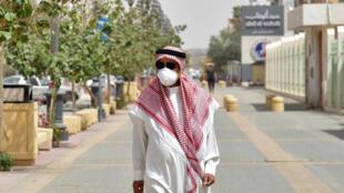 رجل سعودي يرتدي قناعًا وقائيًا  يسير على طول شارع التحلية وسط العاصمة الرياض يوم  15 مارس 2020