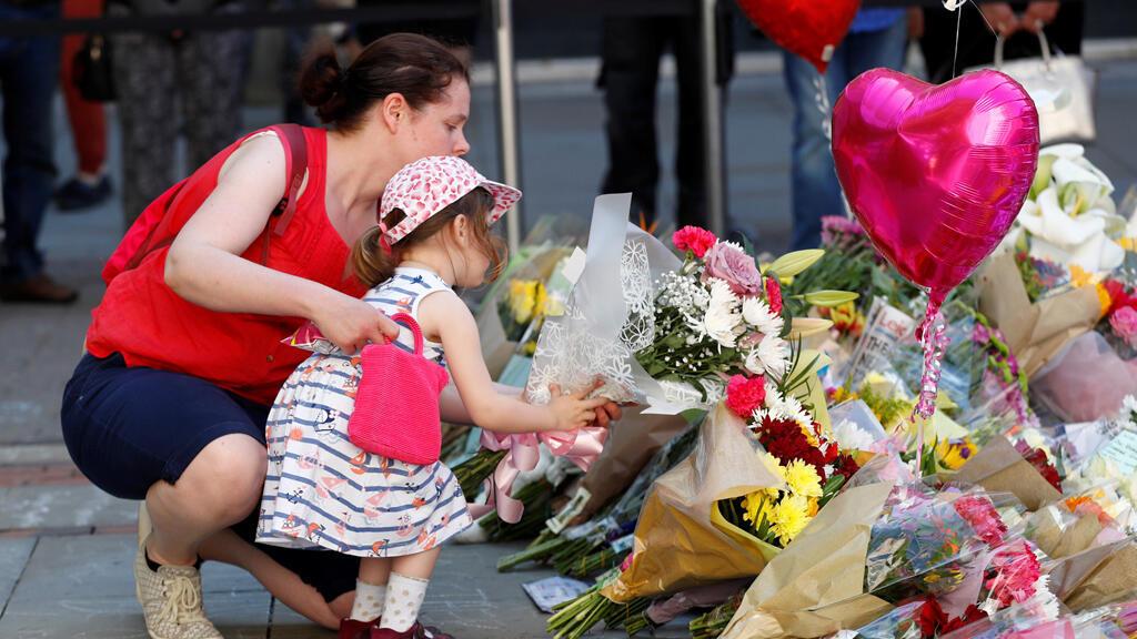 امرأة تساعد فتاة على ترك الزهور تحية لضحايا الهجوم على ساحة مانشستر