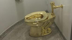 المرحاض الذهبي الصلب ، الذي صنعه الفنان الإيطالي ماوريتسيو كاتيلان ،في متحف غوغنهايم في نيويورك.