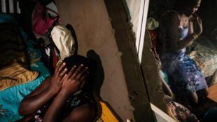 المراهقة لينيت 16 سنة وهي حامل في شهرها الثالث، تغطي وجهها بيدها مع أختها كارول (في المرآة) 22 سنة
