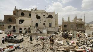 يمنيون يقفون على أنقاض منازل دمرتها غارة جوية بقيادة السعودية في العاصمة اليمنية صنعاء 21 يونيو 2015