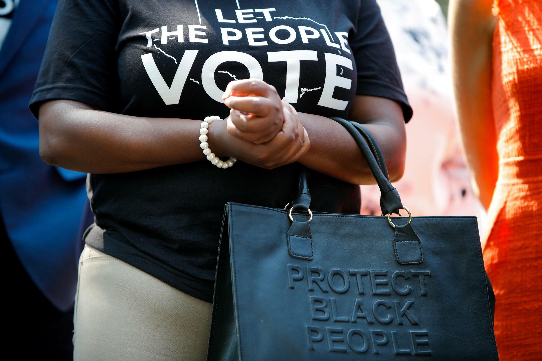 """امرأة سوداء ترتدي قميصا مكتوب عليه """"دعو الشعب يصوت"""""""