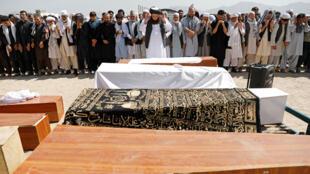 رجال يقيمون صلاة الجنازة على ضحايا انفجار في حفل زفاف في كابول-