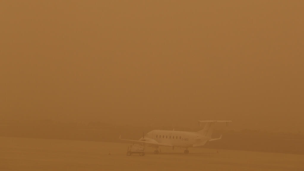 طائرة متوقفة على مدرج أثناء عاصفة رملية   في مطار لاس بالماس ، جزر الكناري