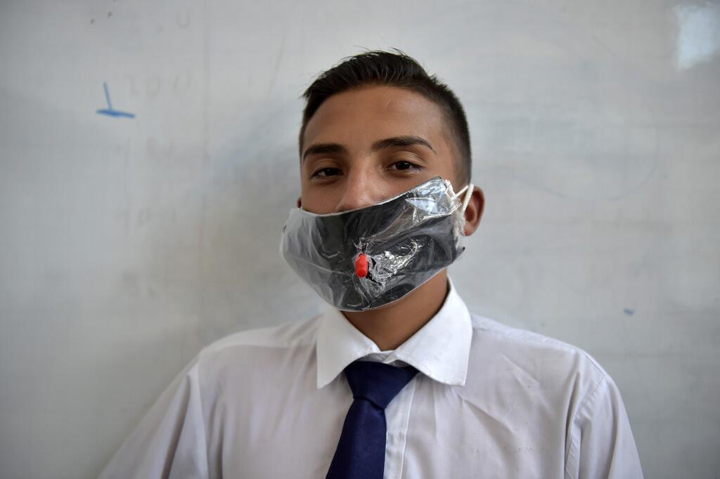 طالب كولومبي يرتدي قناع وجه مصنوع من مواد قابلة لإعادة التدوير وقابلة للتحلل البيولوجي كشكل من أشكال الاحتجاج على نقص أقنعة الوجه في الصيدليات