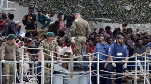 مهاجرون على متن سفينة بريطانية قبل النزول في  إيطاليا، 6 أكتوبر 2015.