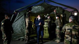 الرئيس الفرنسي إيمانويل ماكرون يرتدي قناعا خلال زيارته للمستشفى الميداني العسكري خارج مستشفى إميل مولر في مولوس ، شرق فرنسا