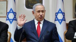 رئيس الوزراء الإسرائيلي بنيامين نتانياهو رافعاً يده خلال كلمة له في مجلس الوزراء