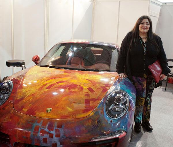 صورة للفنانة التشكيلية السعودية شيلمار شربتلي مع سيارتها البورش