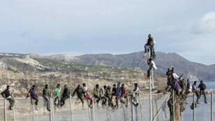 مهاجرون أفارقة يحاولون اجتياز السياج الحدودي بين المغرب واسبانيا