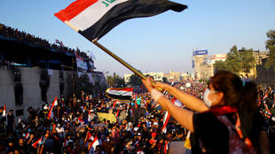 متظاهرة عراقية تلوح بعلم العراق خلال احتجاج مستمر ضد الحكومة في بغداد-