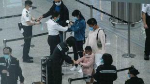 سوار إلكترونية توضع على إيدي مسافرين قادمين لمراقبتهم ووضعهم في الحجر الصحي، مطار هونغ كونغ، الصين