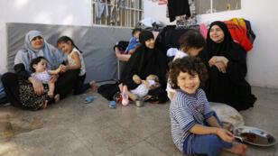 من اليسار إلى اليمين التونسيتان خدوجة الحمري وإيمان عثمان واللبنانية نور الهدى، ثلاث نساء فررن من الرقة مع أطفالهن في مخيم عين عيسى بلبنان