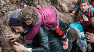مهاجرة تحمل طفلها بعد وصولها إلى شاطئ صخري في جزيرة يونانية 11 أكتوبر 2015.