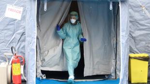 عامل طبي يرتدي قناعا وقائيا عند نقطة تفتيش طبية عند مدخل مستشفى سبيدالي في مدينة بريشيا