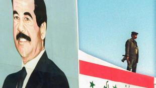 جندي عراقي أمام صورة كبيرة للرئيس الأسبق صدام حسين في بغداد