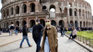 اشخاص يرتدون أقنعة واقية يمشون أمام الكولوسيوم في روما-
