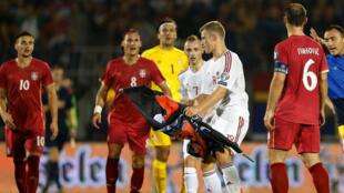لاعب ألباني يحاول الاحتفاظ بالعلم وسط لاعبين صرب