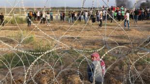 متظاهر فلسطيني مقابل أسلاك شائكة خلال اشتباكات مع القوات الإسرائيلية وسط قطاع غزة 13 أكتوبر 2015