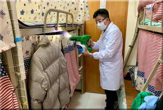 رجل يوضح كيفية رش MAP-1، طلاء مضاد للميكروبات يدّعي فريق الباحثين في جامعة هونغ كونغ للعلوم والتكنولوجيا فعاليته الكبيرة  في قتل الفيروسات والبكتيريا.التجربة  في شقة في هونغ كونغ- 21 أبريل 2020.