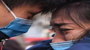 فتاة تبكي بسبب فيروس كورونا وصديقها يواسيها