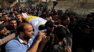 رجال يحملون جثة فلسطيني أثناء تشييع جنازته في جنوب قطاع غزة-