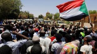 متظاهرون سودانيون يهتفون أمام قوات الأمن