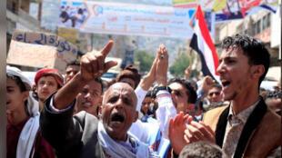 أشخاص يتظاهرون للاحتجاج على الأوضاع الاقتصادية الصعبة في تعز باليمن