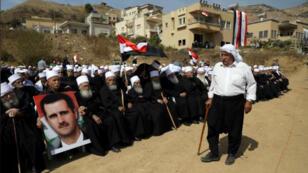 أشخاص من الدروز العرب ينظمون مسيرة ويرفعون صورة للرئيس السوري بشار الأسد قرب خط وقف إطلاق النار بين إسرائيل وسوريا في هضبة الجولان يوم السبت