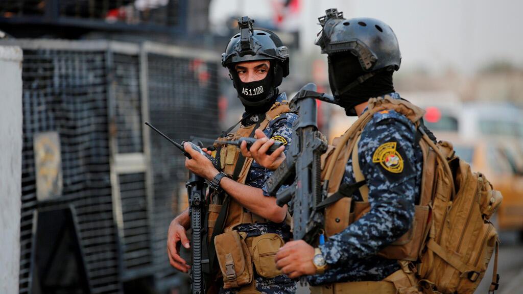 أفراد من الشرطة الفيدرالية العراقية يشاهدون مركبات عسكرية في أحد شوارع بغداد-