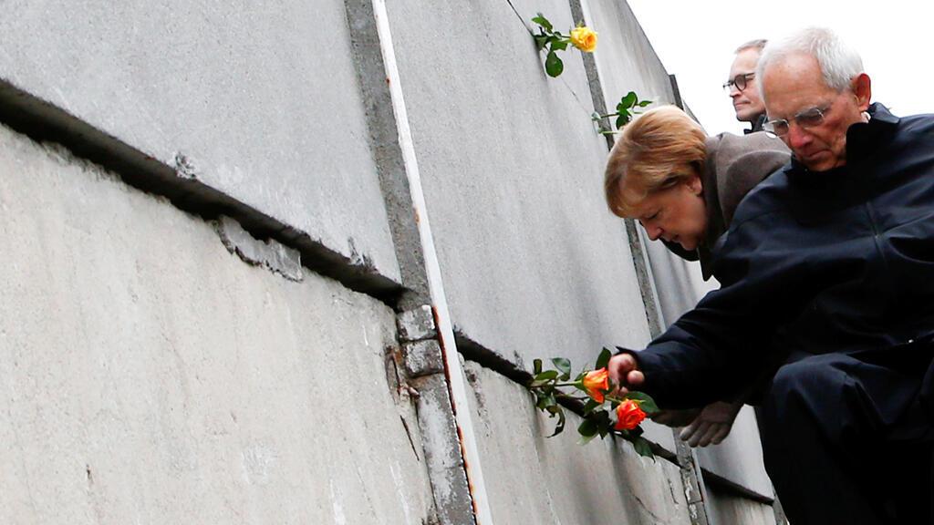 المستشارة الألمانية أنغيلا ميركل ورئيس البرلمان فولفغانغ شويبل يجلسان في النصب التذكاري للجدار خلال حفل بمناسبة الذكرى الثلاثين لسقوط جدار برلين